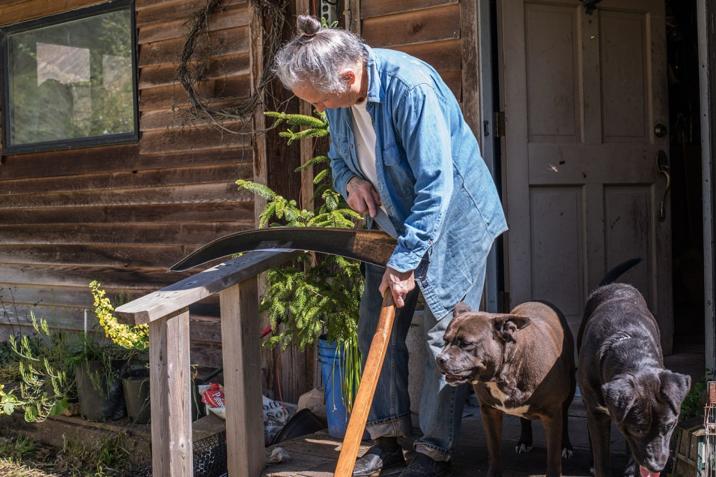 Carol Van Strum prepares to work on her property with her dogs Maybe and Mike at her side in May 2017. Photo: Risa Scott/RF Scott Imagery